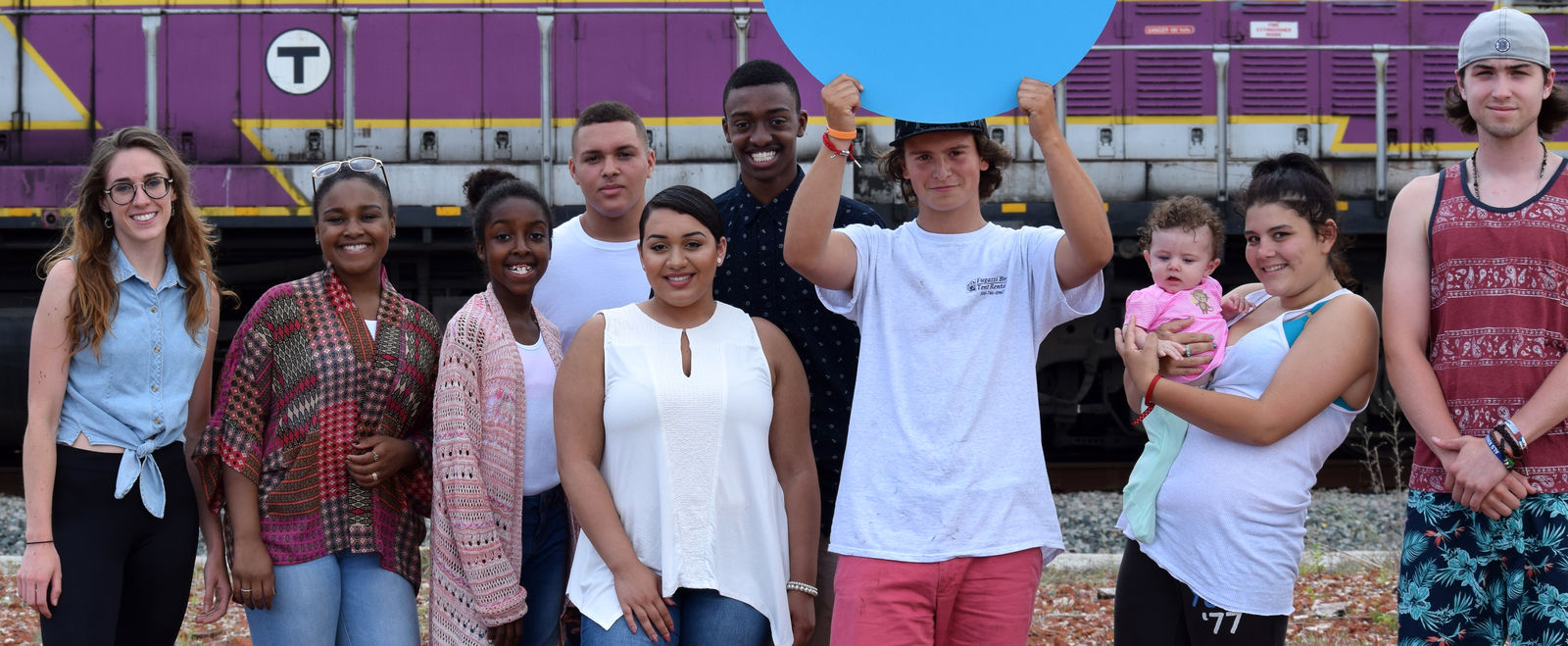 MAP Academy high school students hold up their school sign in front of a passing commuter rail train.