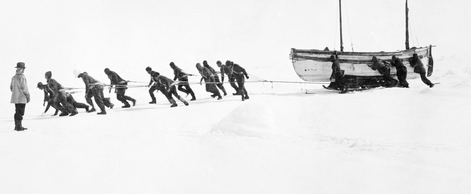 Men work together to haul a boat ashore.