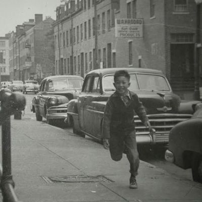 Historic photo of young boy on sidewalk in Boston Chinatown