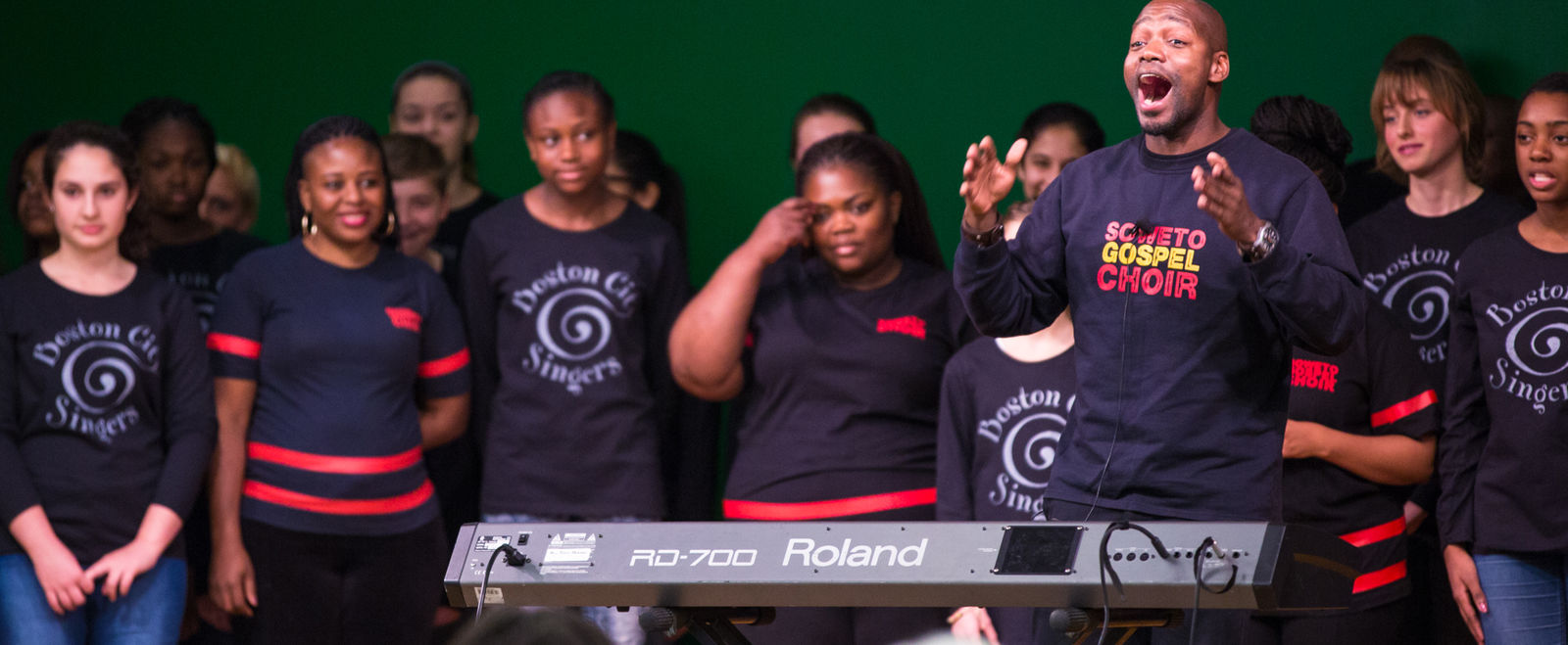 Soweto gospel troupe performs with a piano and chorus on stage.