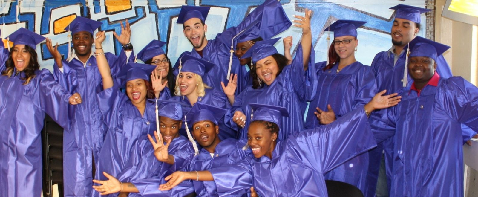 Students in their graduation poses smile and pose for the camera with goofy faces.