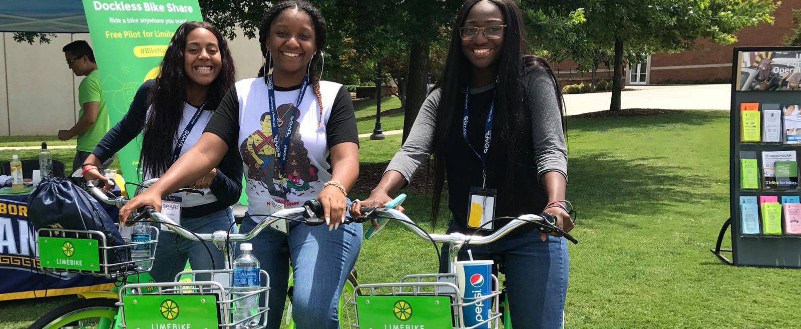 Three girls pose for a picture on their dockless Limebikes.