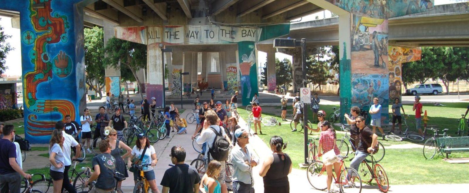 Bikers and pedestrians hang out under a street mural.