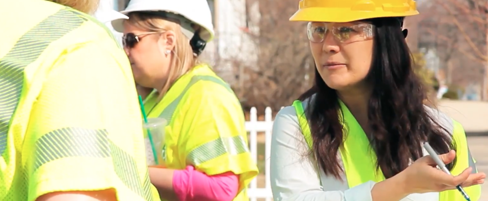 A woman in a hard hat talks to other women while measuring gas leaks.