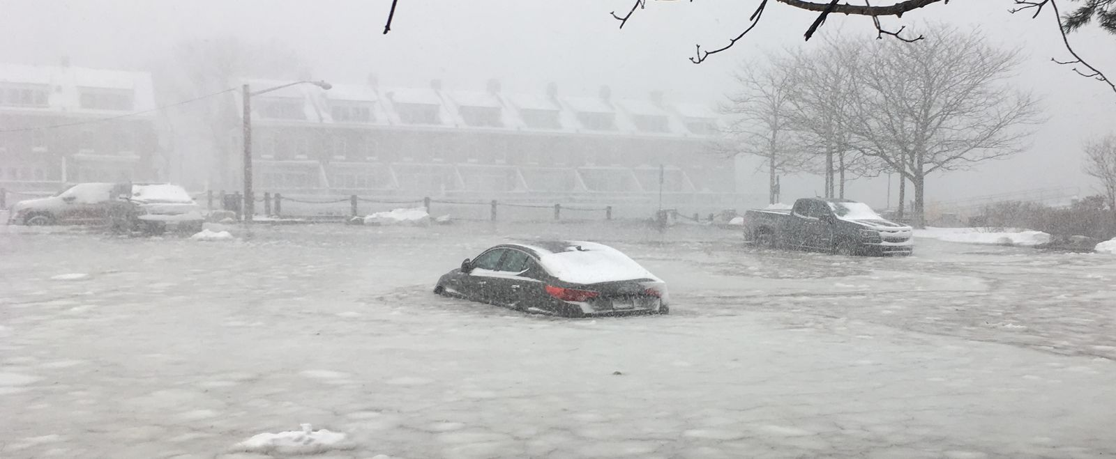 Cars parked by Boston's waterfront and flooded by snow and water.