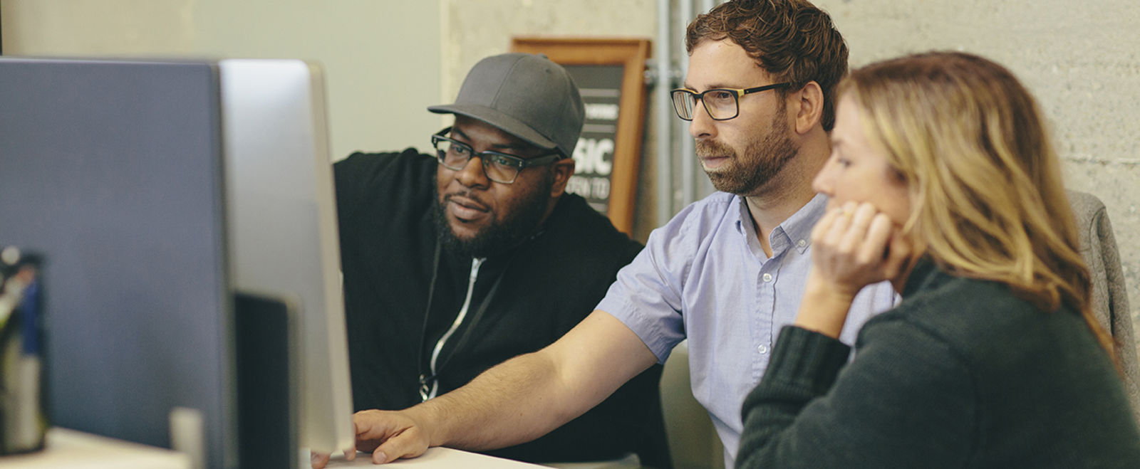 Three Sonos employees collaborating on a computer.