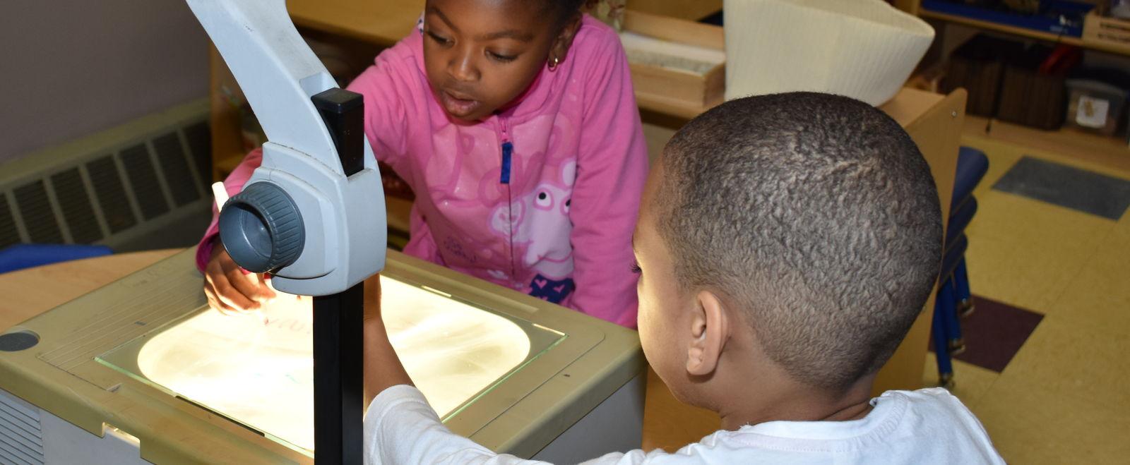 Two kids writing on an overhead projector in preschool