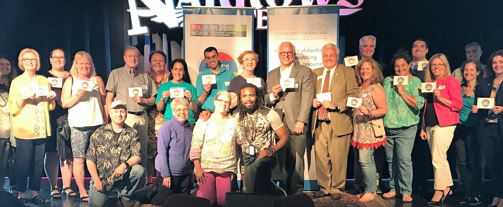 A group of adults pose on a stage to support a fundraiser for a community foundation.