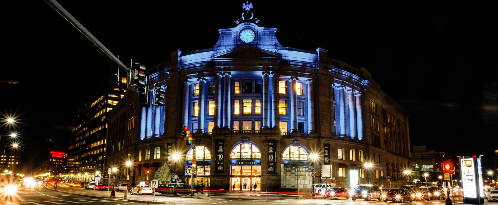 Boston's South Station is lit up by blue lights at night.
