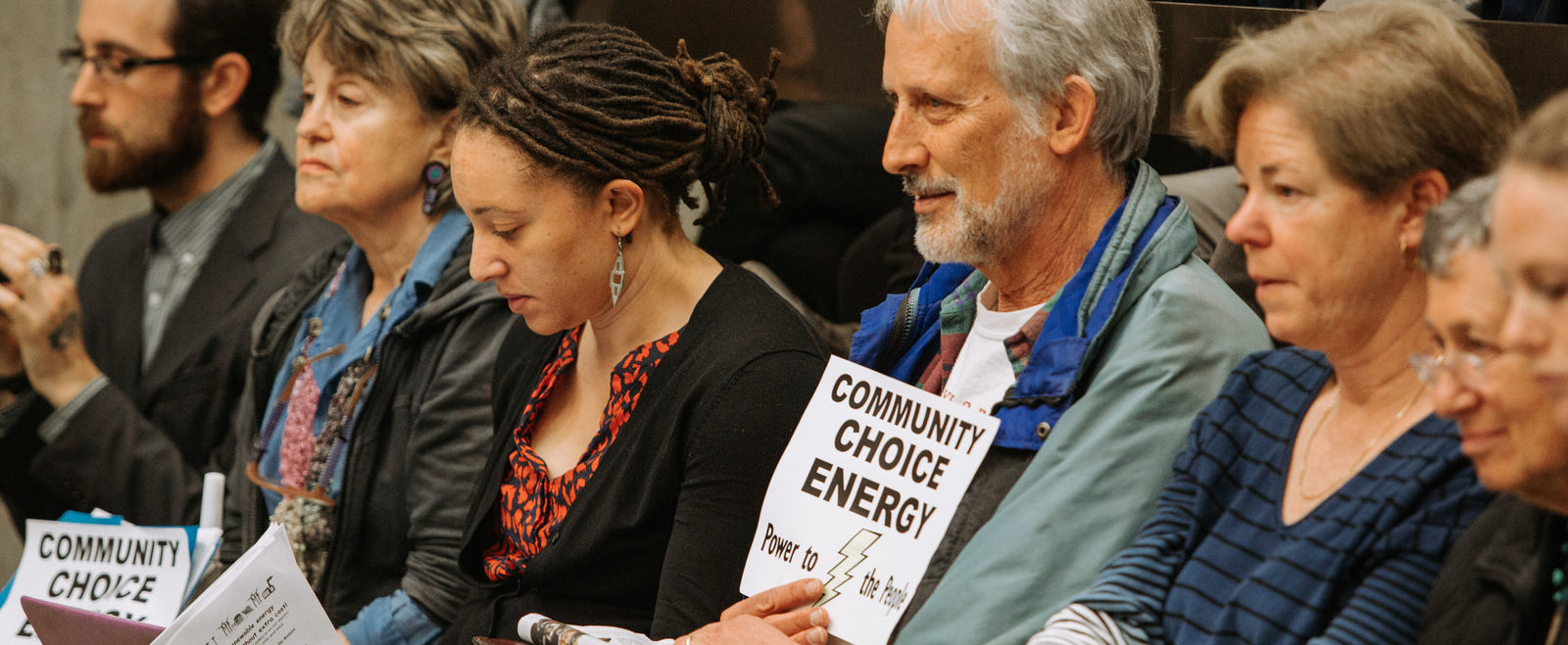 Activists sit and hold signs at the CCE city council meeting.