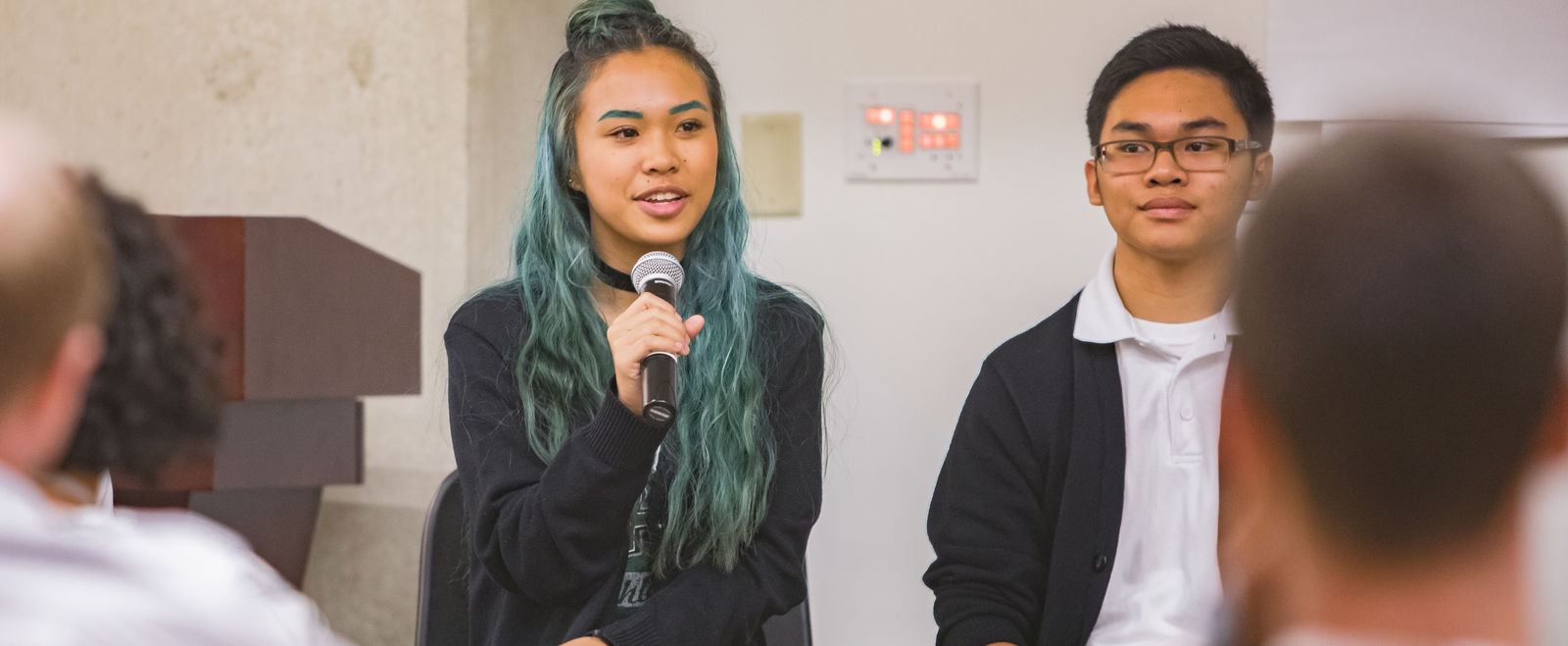Two students answer questions during a school panel discussion.