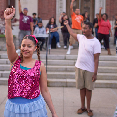 Kids pump their fists during a musical performance.