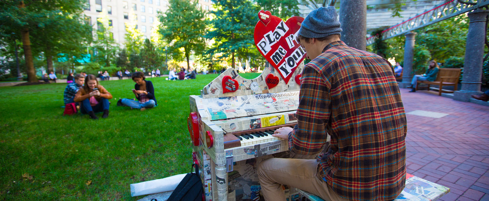 Man playing a piano in an outdoor park