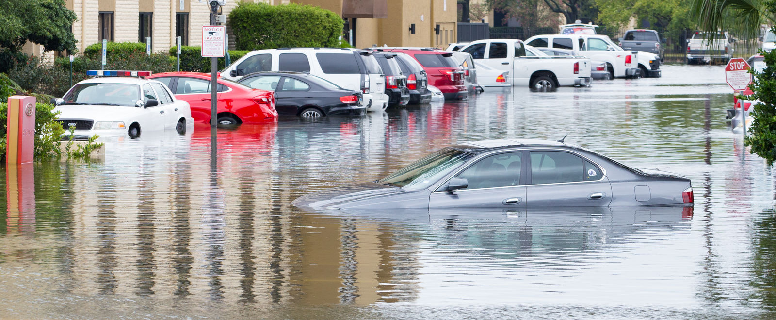 A parking lot in a city floods in a storm.