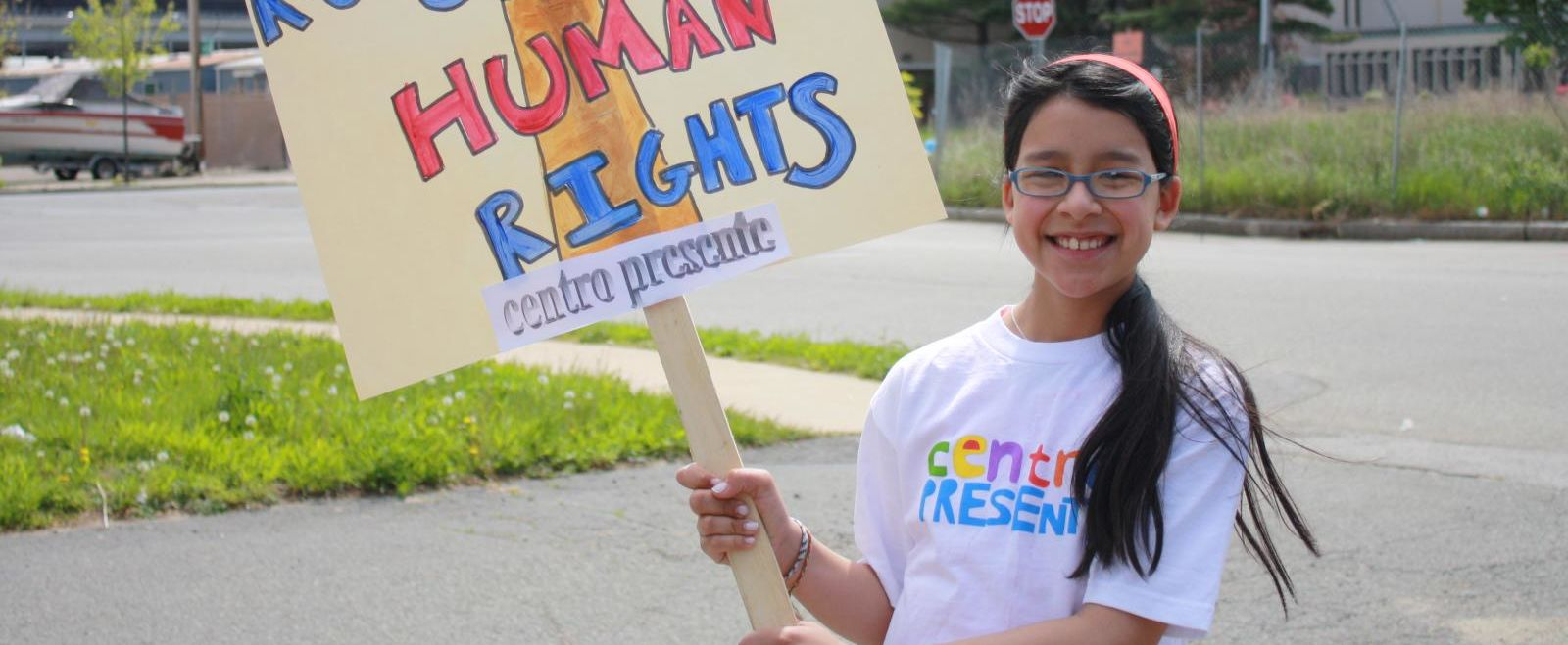 """Girl holding a sign that says """"Immigrant rights are human rights."""""""