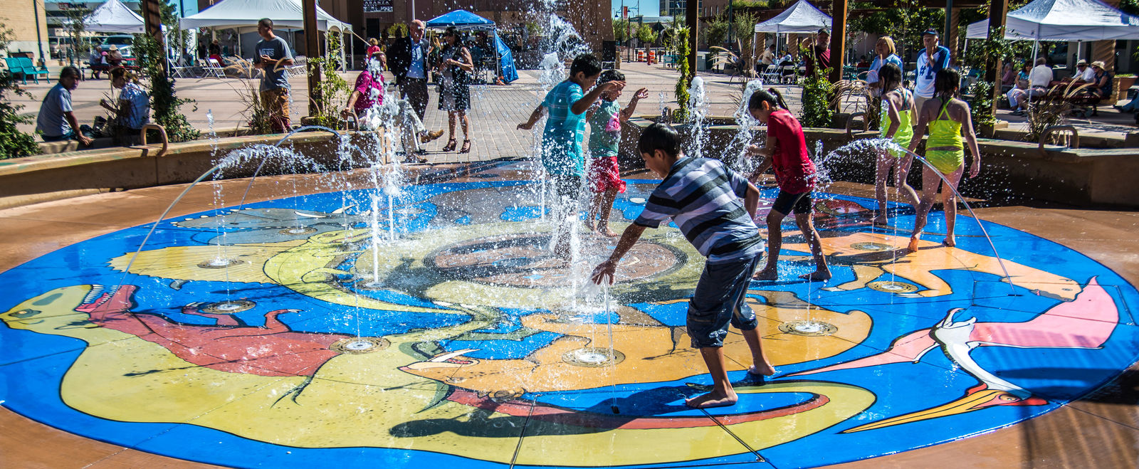 Kids play outside at a public water park in New Mexico.