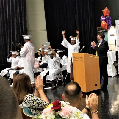Students sit on stage in their graduation gowns and cheer.