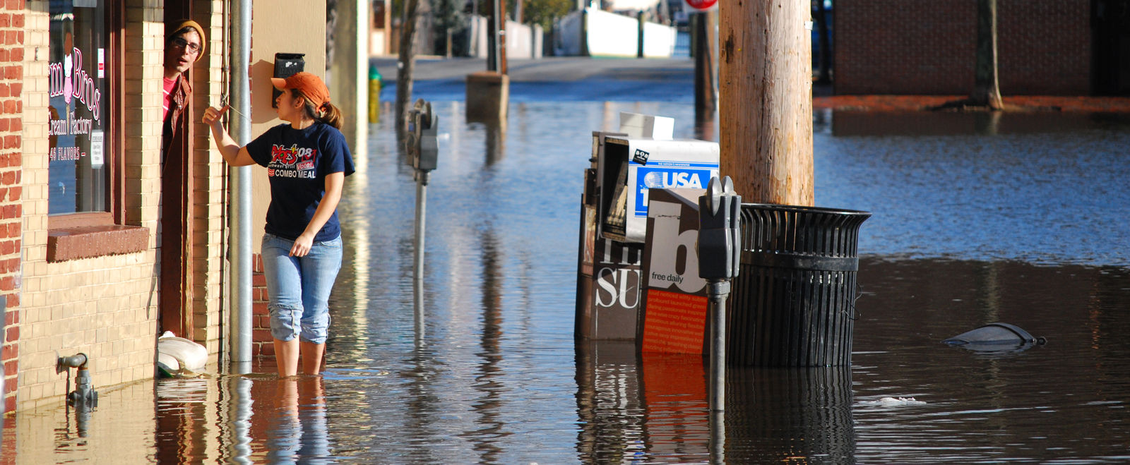 A woman stands in a town center with flooded streets and sidewalks.