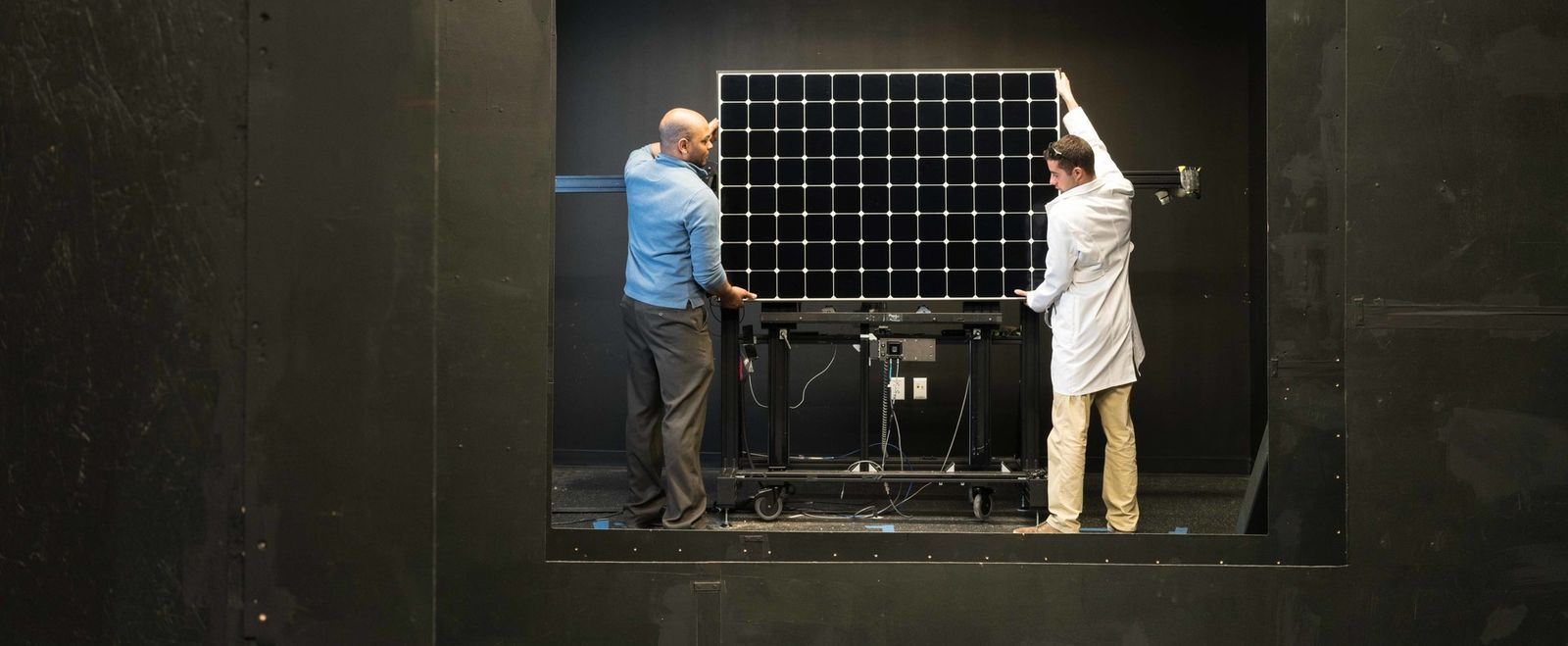 Two men mount a PV module for performance testing in a solar simulator dark tunnel.