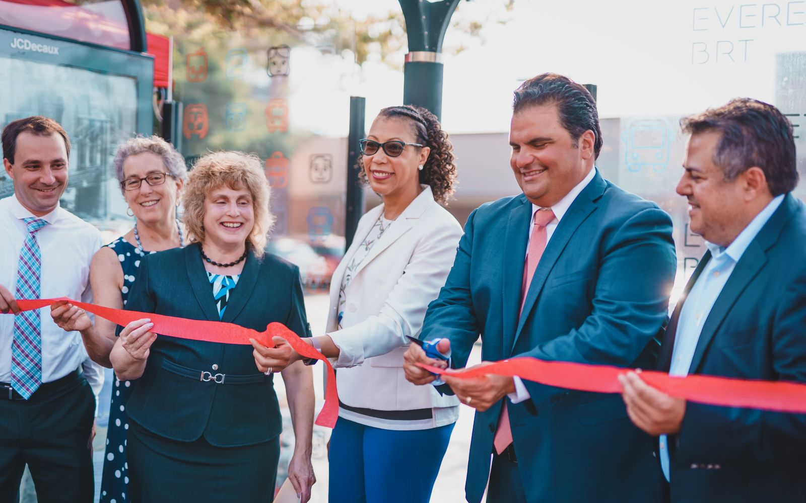 People standing behind a red ribbon at a ribbon cutting ceremony.