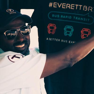 Bus driver holding up a EverettBRT shirt