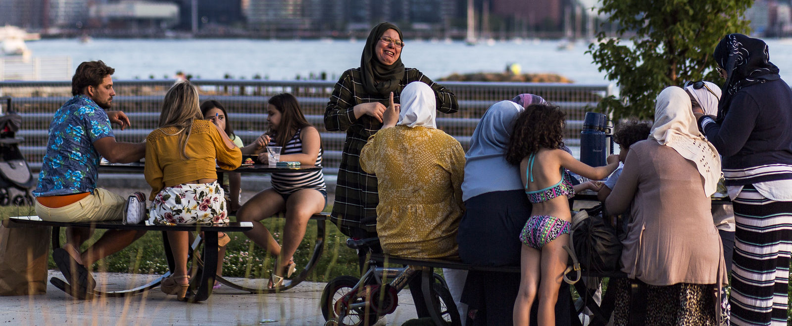 People laugh at picnic tables on Boston's waterfront.