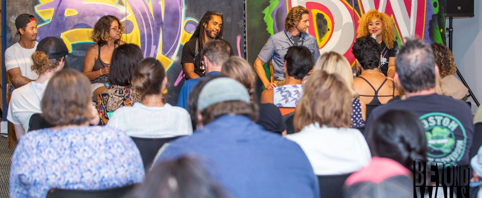 Artists speak on a panel in front of an audience.