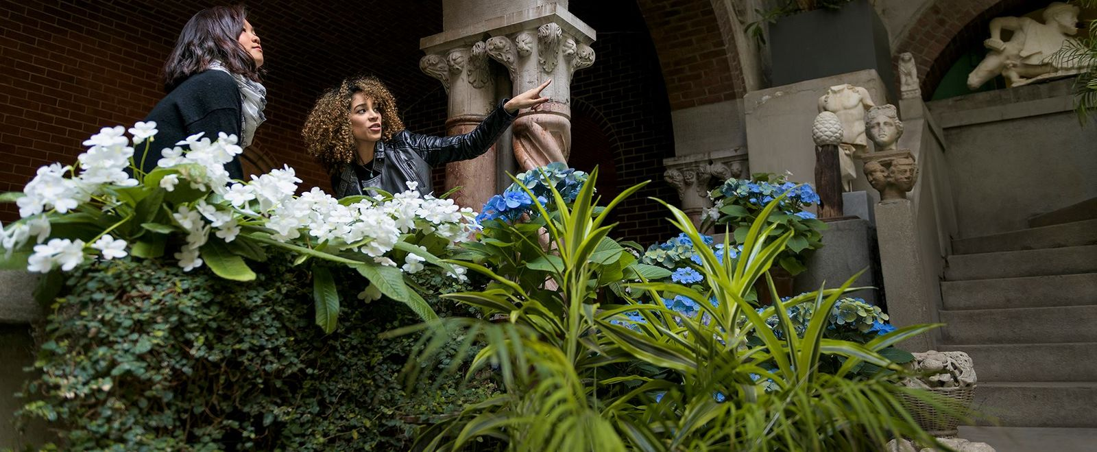 Two women point and talk at the Isabella Stewart Gardner Museum.