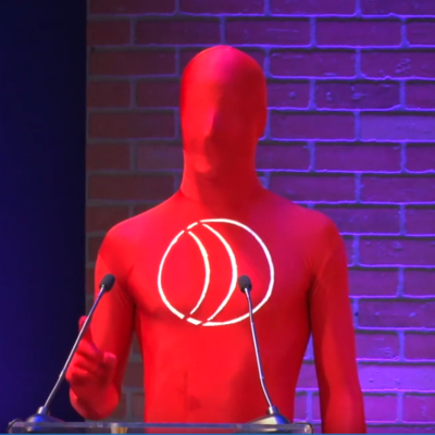Stefan Lanfer in full lycra bodysuit, opening the 2018 Annual Conference of the Communications Network.