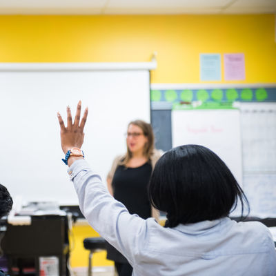 Two students raise their hands in a high school classroom.