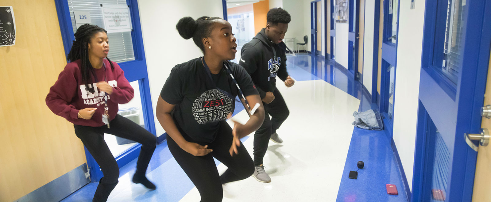 Three students practice a dance routine in their high school hallway.