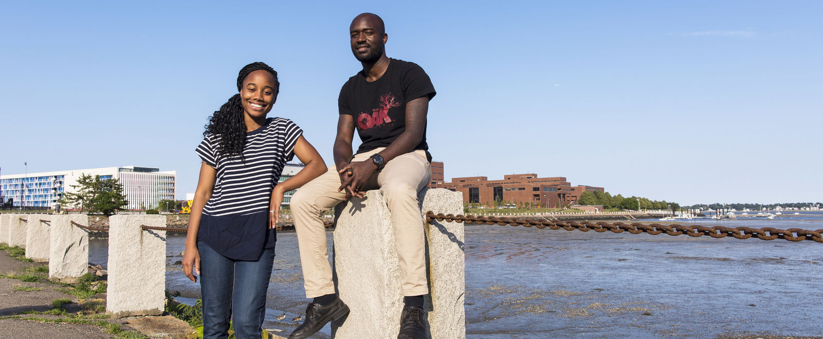Two people smile on the Boston Harbor.