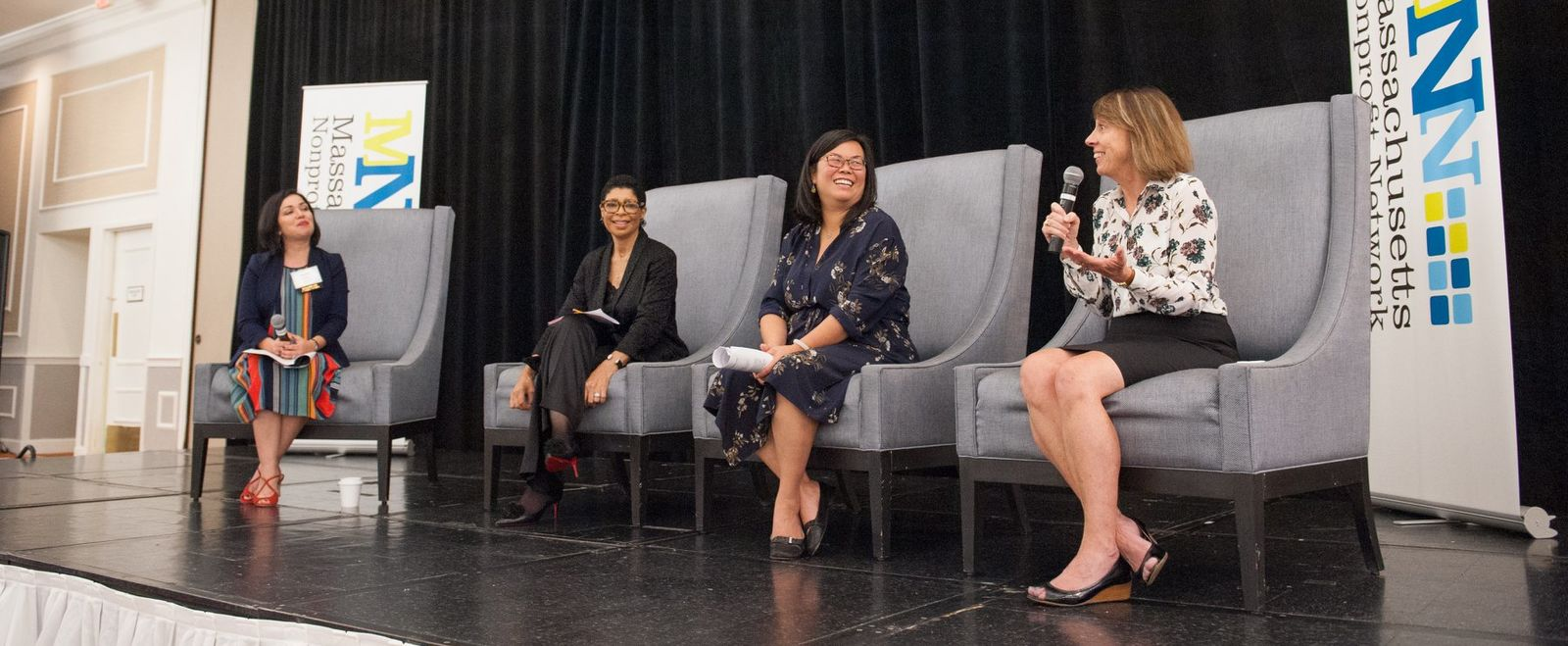 Four women speak on stage at a panel discussion.