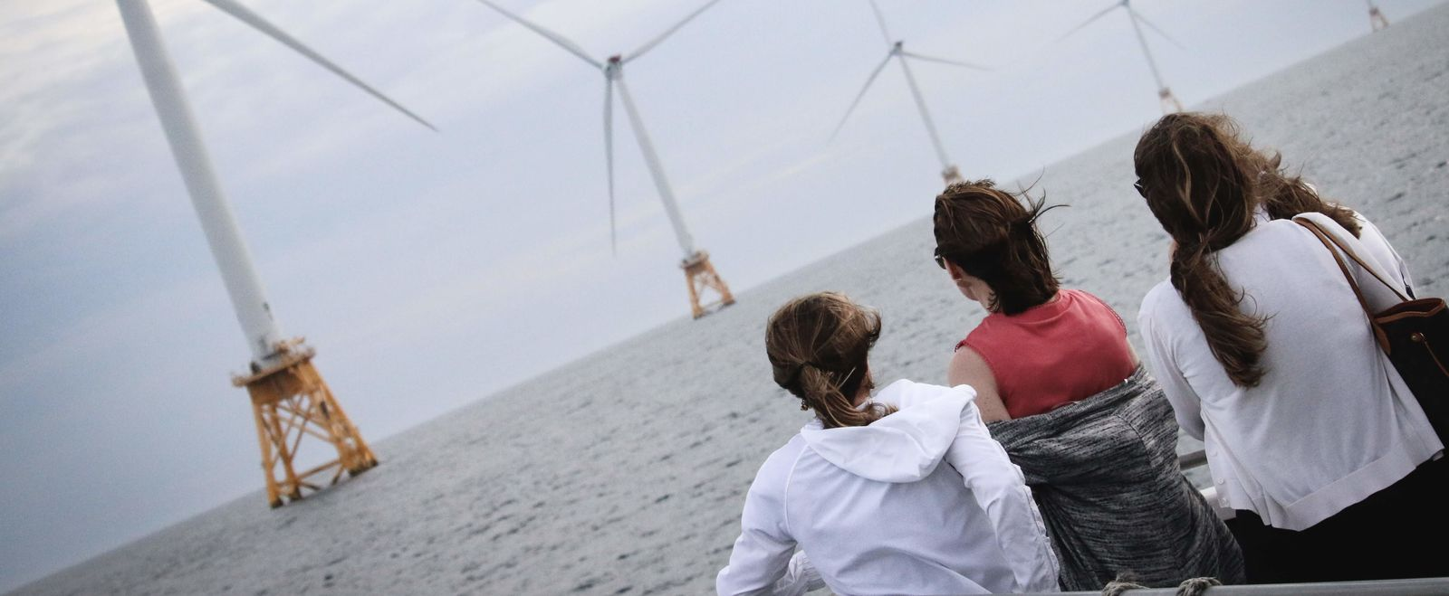 Three women look at offshore wind turbines from a cruise.