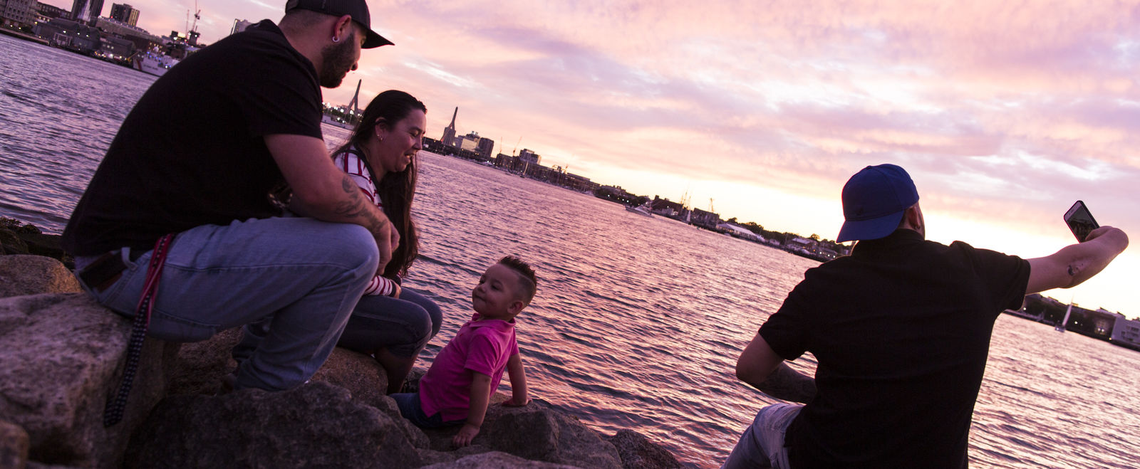 A family sitting on rocks at the edge of Boston Harbor at sunset