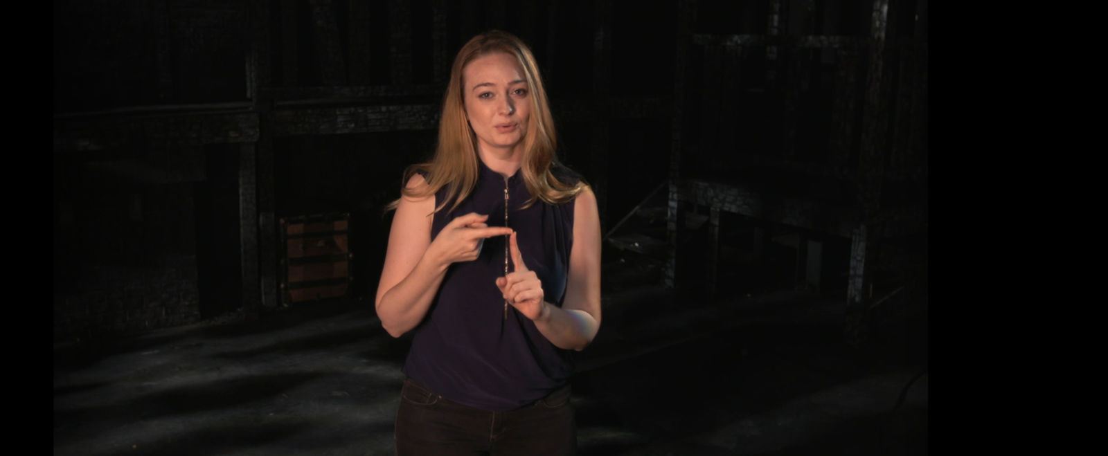 A woman uses American sign language on stage.