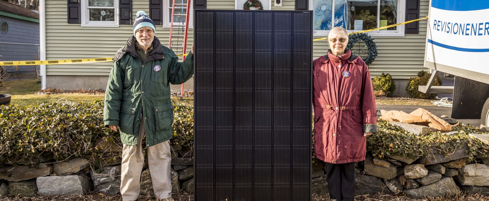 A couple poses with solar panels.