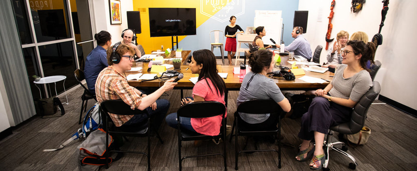 People gather at a table to work on a podcast.