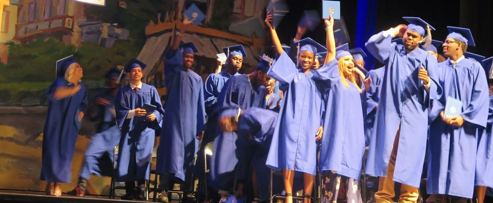 Students raising their hands on stage on graduation day.