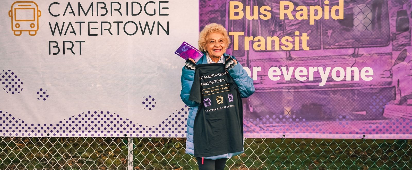 Elderly woman holding up a BRT t-shirt and smiling.