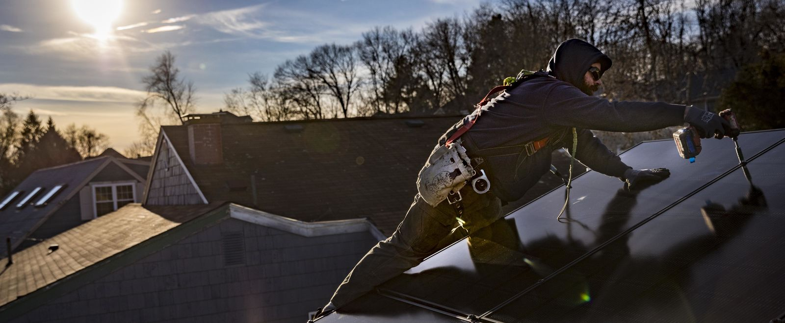 A man installs solar panels on a roof in Lowell.