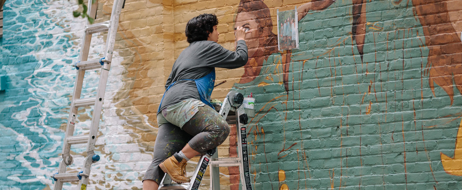 A woman paints a mural outdoors.