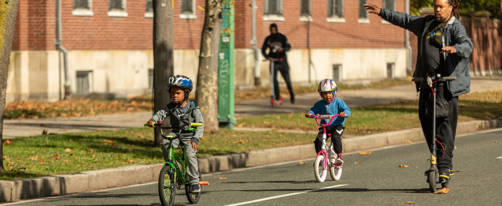 A family bikes on open streets.