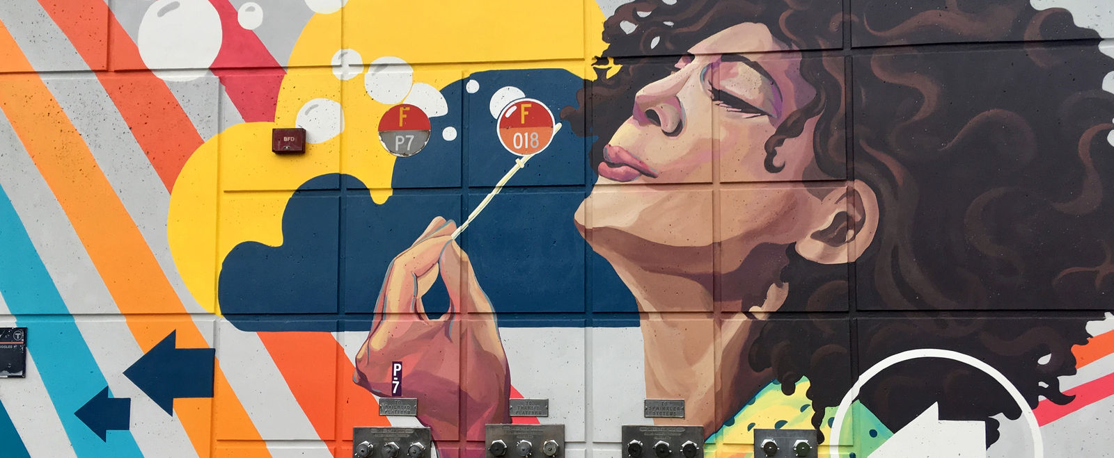Colorful mural of woman with brown hair and red lipstick blowing white bubbles across a rainbow.