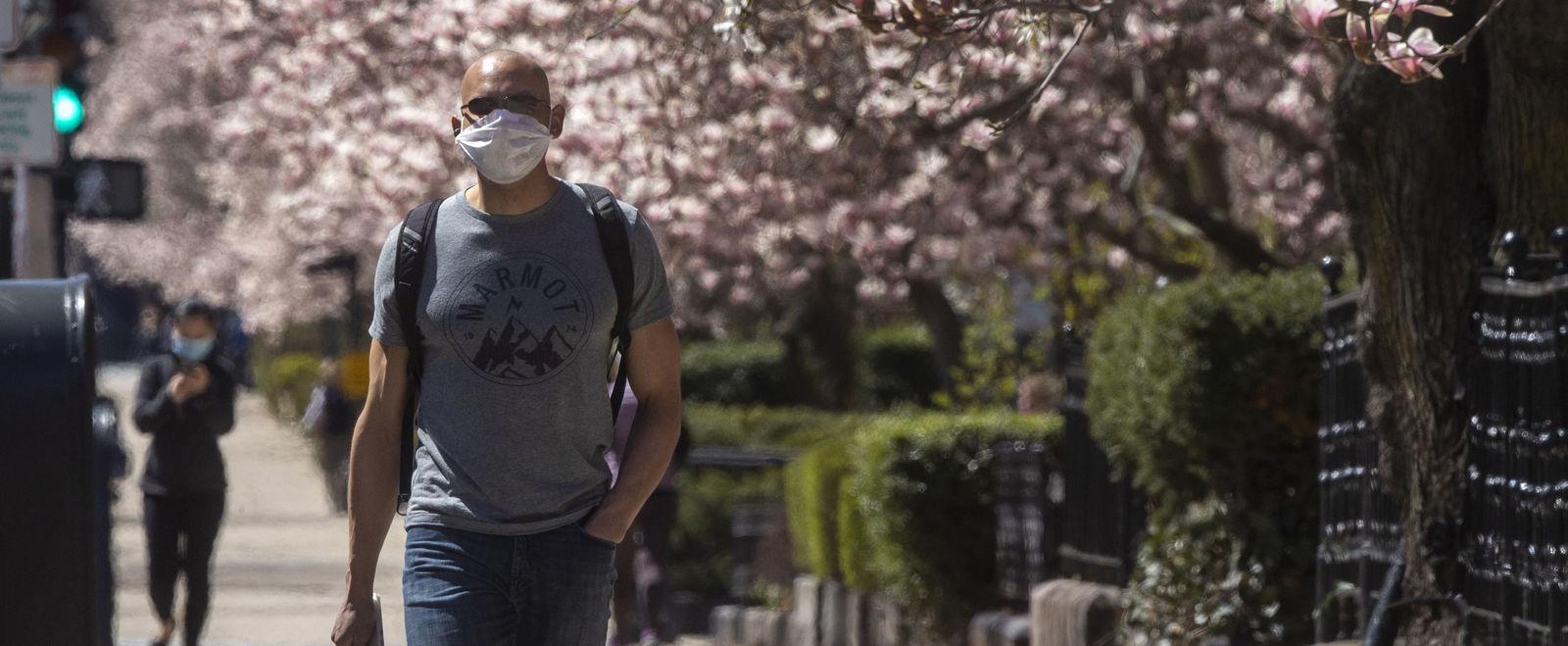 A masked man walks in Boston during spring.
