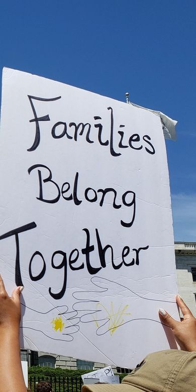 """Image of protest at Massachusetts Statehouse over family separations, with poster reading """"Families Belong Together"""""""