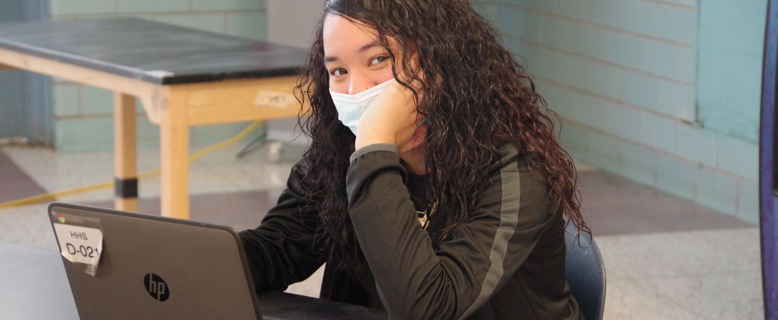 girl smiles at laptop in a high school cafeteria