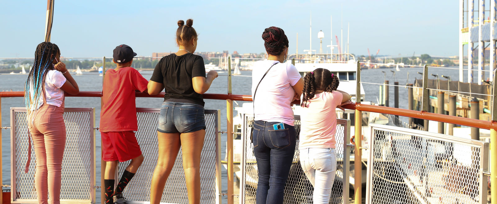 Young people look out at the Boston skyline from a boat.