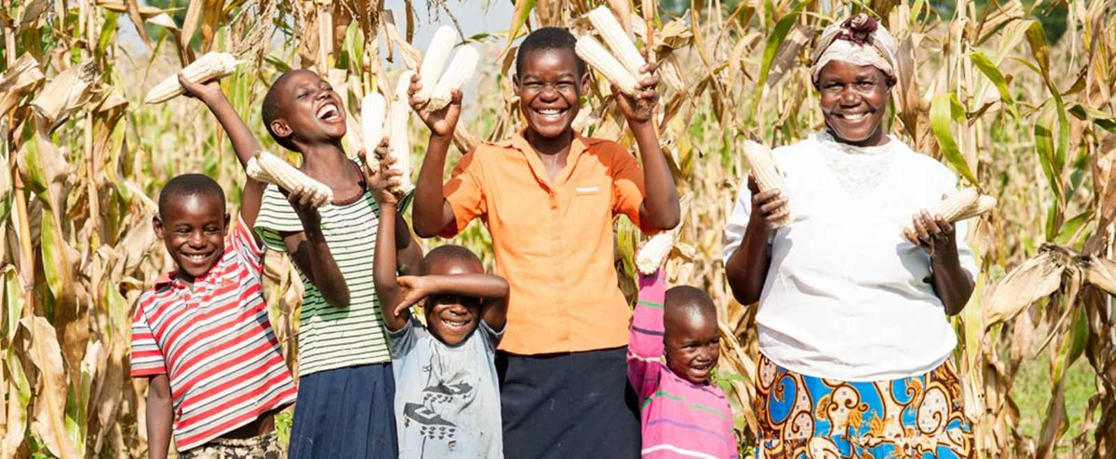 A family smiles and holds up husks of corn outside.