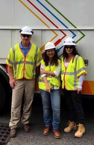 Three people smile in front of a utilities truck.